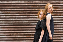 Two Red Headed Girls In Black Dresses Back To Back Against Rusty Brown Corrugated Iron Shed