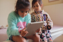 Multicultural Kids Using Tablet In Bedroom