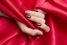 Closeup Shot Of A Female's Hand With Beautiful Nail Polish Caressing A Red Silk Fabric