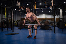 Aggressive Sportsman Deadlifting Barbell In Gym