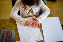 Above-view Of A Small Child Sitting At A Table Writing A Story