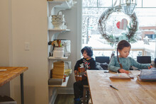 Two Children Sit Together In Kitchen Creating Music And Art By Window