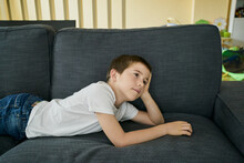 Boy With A Thoughtful Attitude Lying On A Sofa