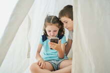 Boy And Girl Looking At A Smartphone Inside A White Teepee Tent Inside Their House. Technology Concept