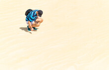 Young Man Crouching In The Dunes Of A Desert On A Sunny And Hot Day.