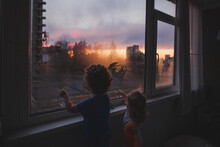 Children Sit At Home With Their Fingers Drawing On The Window At Sunse