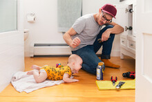 Father Fixing Kitchen Sink While Baby Girl Lying On Hardwood Floor At Home
