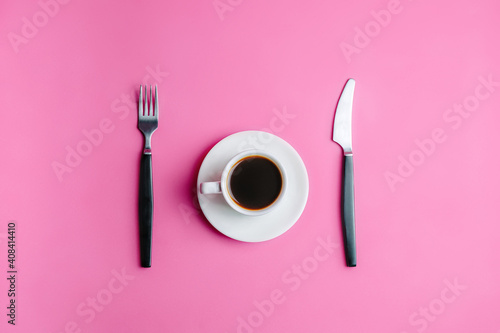 Cup of coffee with a fork and knife on a pink background. Diet food