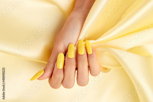 Photo Closeup shot of a female's hand with yellow nail polish on a yellow silk fabric