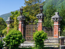 Details Of The Elaborate Wrought Iron Gate Of Villa Pessina. Gateway To The Pessina Castle. Tremezzo, Como Lake, Italian Lakes, Italy.
