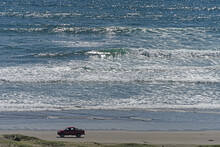 Red Car On The Cost With A Beautiful Seascape In The Background