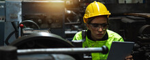 Engineer Woman Wearing Helmet And Reflective Vest In Check And Control Industrial Machine On Tablet In Industry,