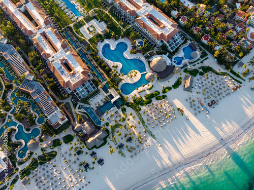 Obraz Aerial drone view of beach resort hotels with pools, umbrellas and blue water of Atlantic Ocean, Bavaro, Punta Cana, Dominican Republic - fototapety do salonu