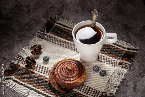 Fototapeta Tea in a white mug with a handle, spoon, with a bun snail with cinnamon on a napkin, on a gray background obraz