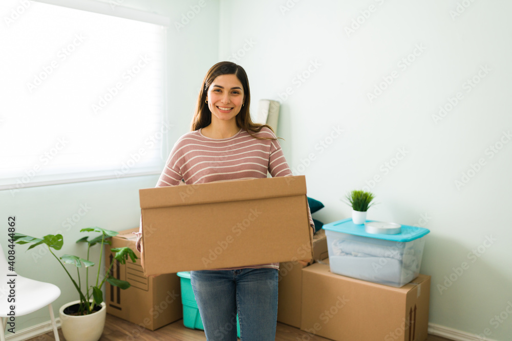 Fototapeta Happy young woman carrying a package in the living room
