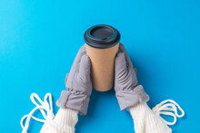 Hands Of A Girl In A White Sweater And Mittens With A Paper Cup Of Coffee On A Blue Background.