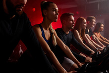 Fit People Exercising And Working Out In Gym, Cycling Machine Bicycle, Wearing Tracksuit. Training, Healthy, Wellness In Fitness