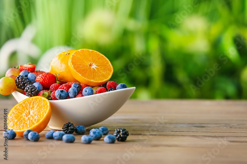 Obraz Bowl with different fruits and berries on table outdoors - fototapety do salonu