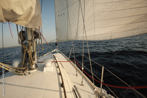Fototapeta White sloop rigged yacht sailing in an open sea at sunset. Clear sky. A view from the deck to the bow, mast, sails. Transportation, travel, cruise, sport, recreation, leisure activity, racing, regatta obraz na płótnie