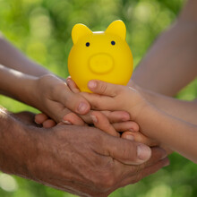 Family Holding Piggy Bank In Hands Against Green Spring Background
