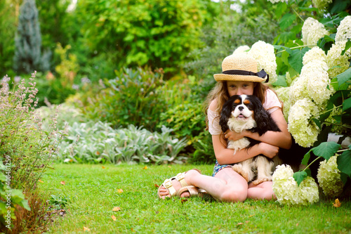 Obraz na plátne happy kid girl relaxing with her cavalier king charles spaniel dog in summer gar