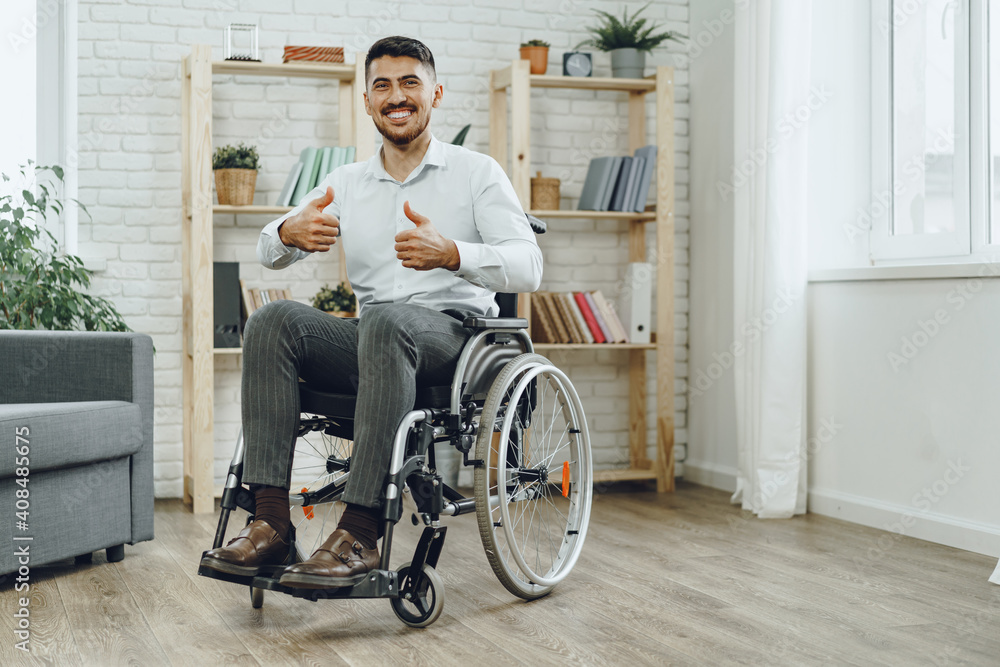 Fototapeta Happy smiling young man in a wheelchair at home