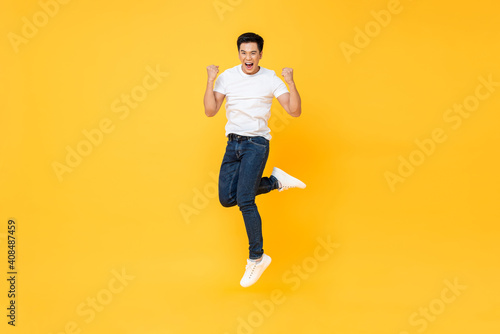 Obraz Happy energetic young Asian man jumping yelling and clenching fists isolated on yellow studio background - fototapety do salonu