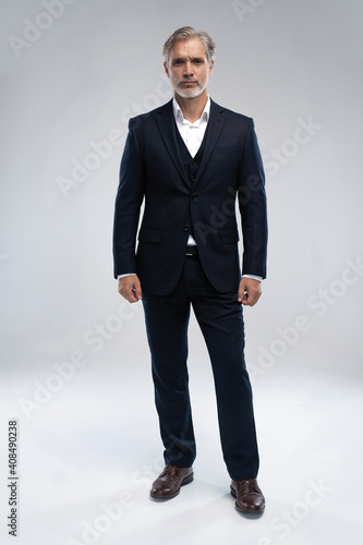 Obraz Full length shot of a mature businessman wearing a suit looking at camera - fototapety do salonu