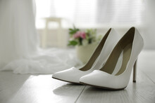 Pair Of White High Heel Shoes And Blurred Wedding Dress On Background, Space For Text