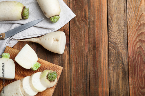 Fotografie, Obraz White turnips on wooden table, flat lay. Space for text