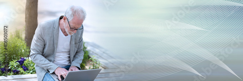 Mature businessman using laptop outdoors; panoramic banner