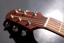 Music And Musical Instruments Concept - Close Up Of Acoustic Guitar Head With Pegs