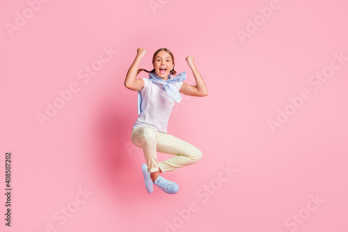 Obraz Full size photo of hooray girl fists up wear white t-shirt sweater trousers sneakers isolated on pink background - fototapety do salonu