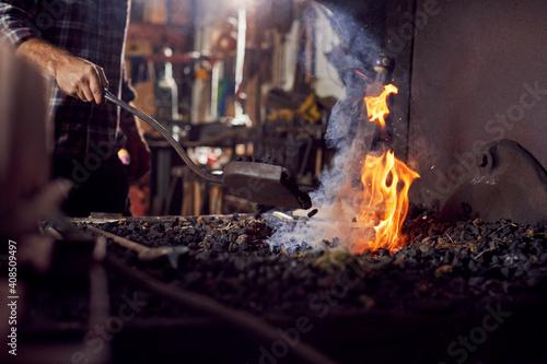 Fototapeta Male Blacksmith Adding Coal Fuel To Wood Kindling To Start Blaze In Forge