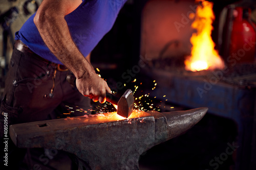 Canvas Print Close Up Of Male Blacksmith Hammering Metalwork On Anvil With Sparks And Blazing