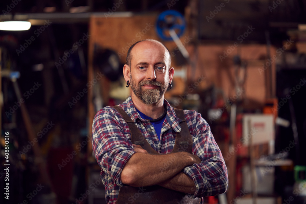 Fototapeta Portrait Of Mature Male Blacksmith Standing In Forge With Folded Arms