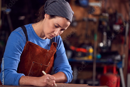 Fotografie, Obraz Female Blacksmith Wearing Headscarf Working On Design In Forge