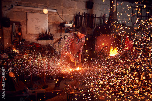 Fotografia Male Blacksmith Hammering Metalwork On Anvil With Blazing Forge In Background