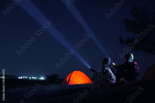 Obraz Couple with flashlights near camping tent outdoors at night - fototapety do salonu