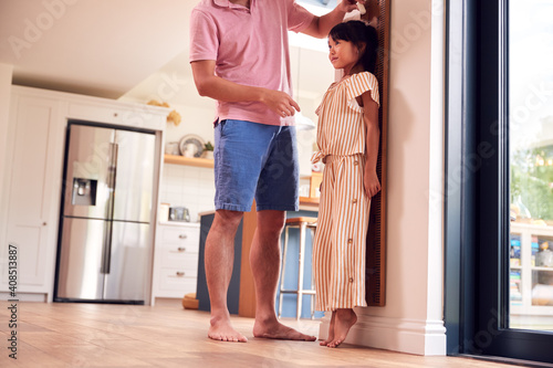 Fotografía Asian Father Measuring Daughter On Wall Scale At Home As She Stands On Tip Toes
