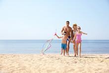 Happy Family With Kite At Beach On Sunny Day