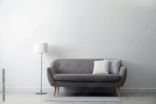 Grey sofa with pillows near white wall in stylish living room interior © New Africa