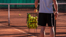 Tennis Coach Conducts Training On Red Clay Court, Basket With Tennis Balls Near Him. Blurred Background. Sports Activity And Leisure Concept. Lifestyle