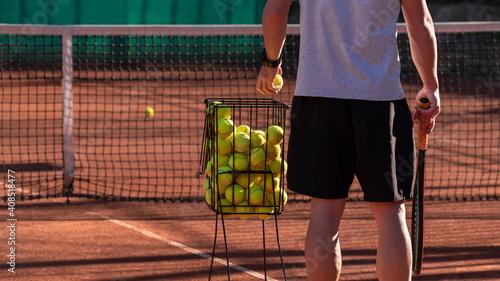 Cuadros en Lienzo Tennis coach conducts training on red clay court, basket with tennis balls near him
