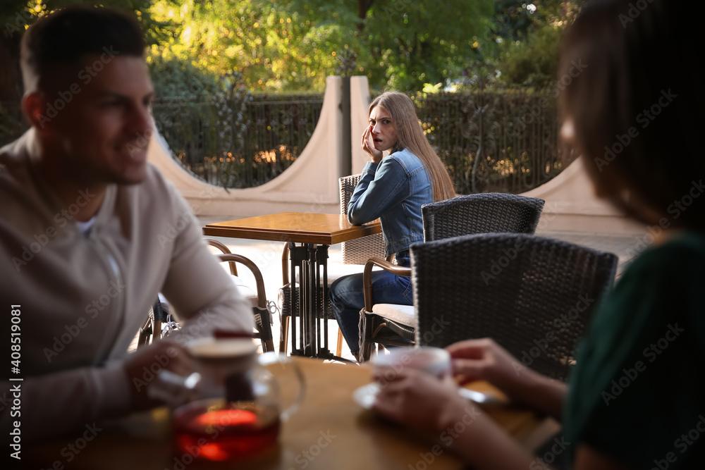 Fototapeta Jealous ex girlfriend spying on couple in outdoor cafe