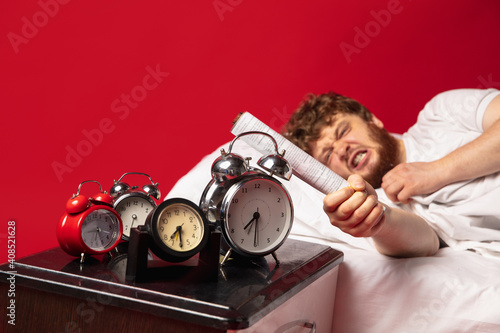 Obraz na plátně Man wakes up at his bed on red background and he's mad at clocks ringing, switches it off with rolled documents