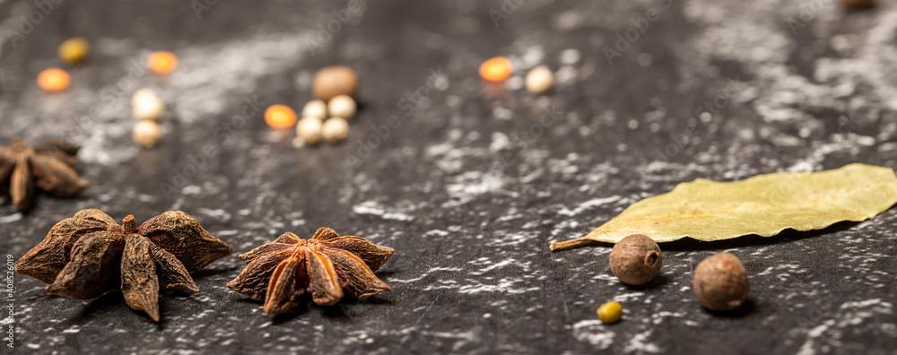 Fototapeta Anise stars Illicium verum, black peppercorns on black stone background. Selective focus, banner