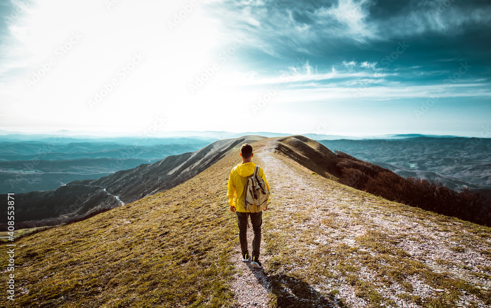 Fototapeta Hiker with backpack hiking on the top of a mountain - Man walking on forest path at sunset - Focus on the guy