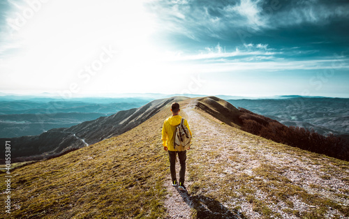 Hiker with backpack hiking on the top of a mountain - Man walking on forest path at sunset - Focus on the guy  - fototapety na wymiar
