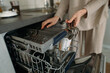 woman unloads dishes from the dishwasher
